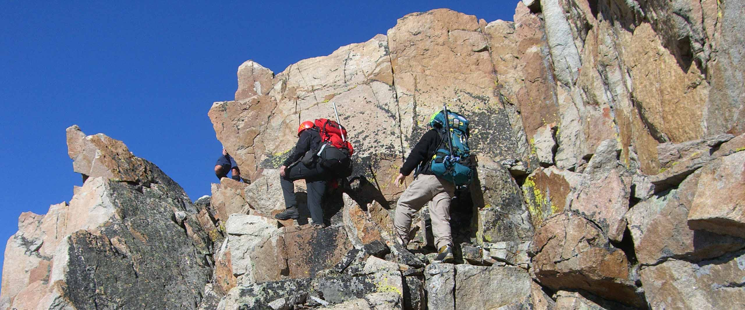 image of hikers scrambling up the side of a mountain.