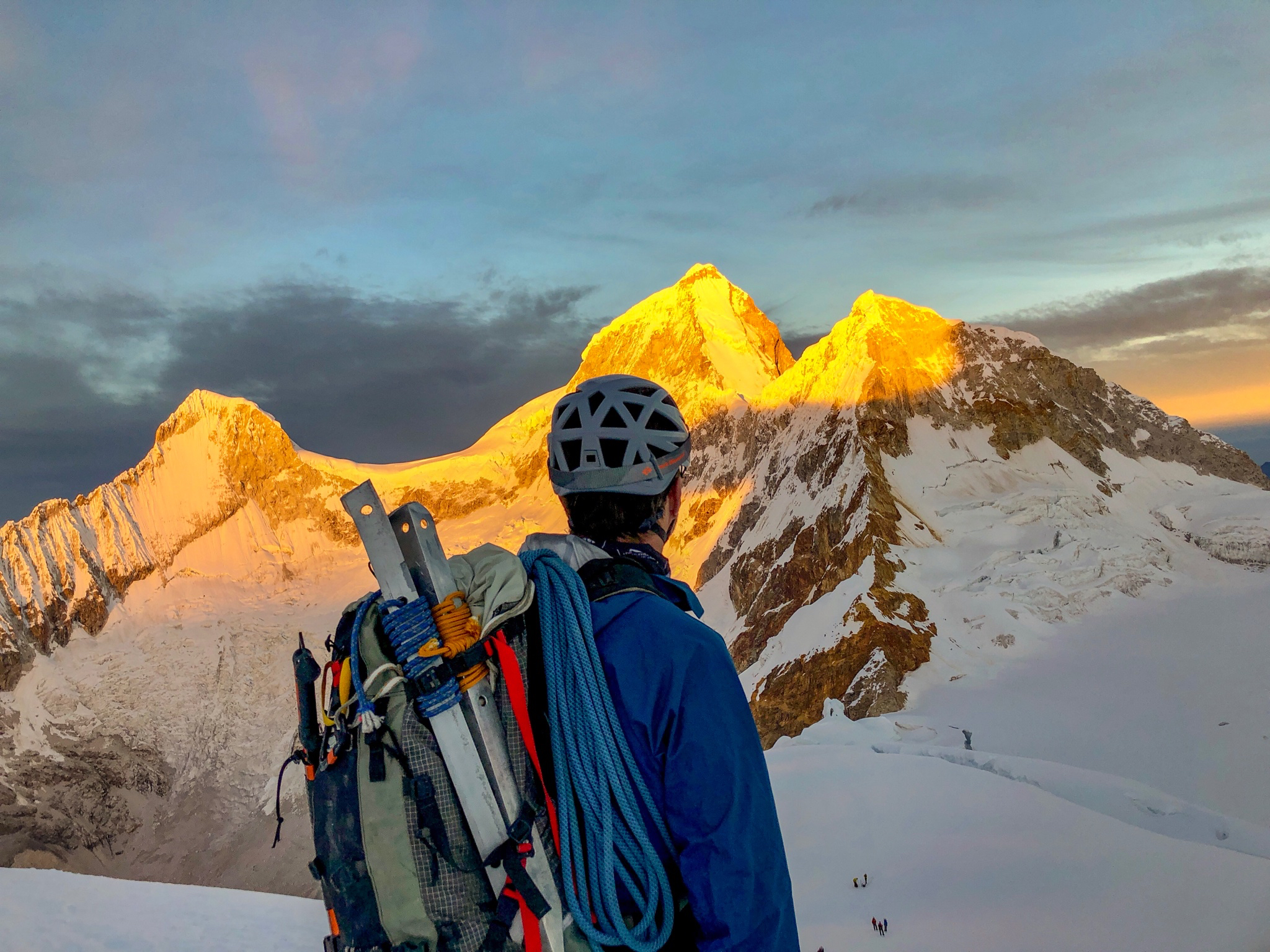 Man with climbing gear looking at sun rise on mountains