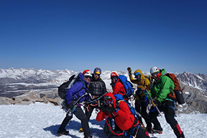 Group of people in helmets and winter coats on a snow coated mountain summit
