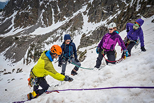 three people learning from one person on ice about climbing while on snow