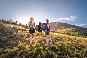Ladies standing in three, with packs and trekking poles, looking out at green mountains to conquer