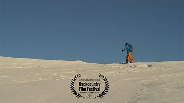 Backcountry Film Festival BSI Film Selected - person skinning up a slope with blue sky