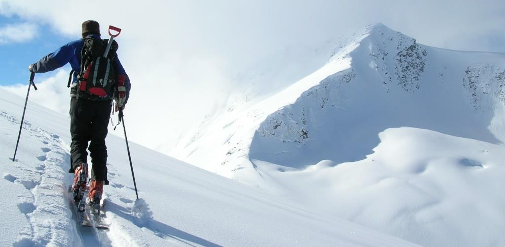 man hiking up on skis to the top of a mountain