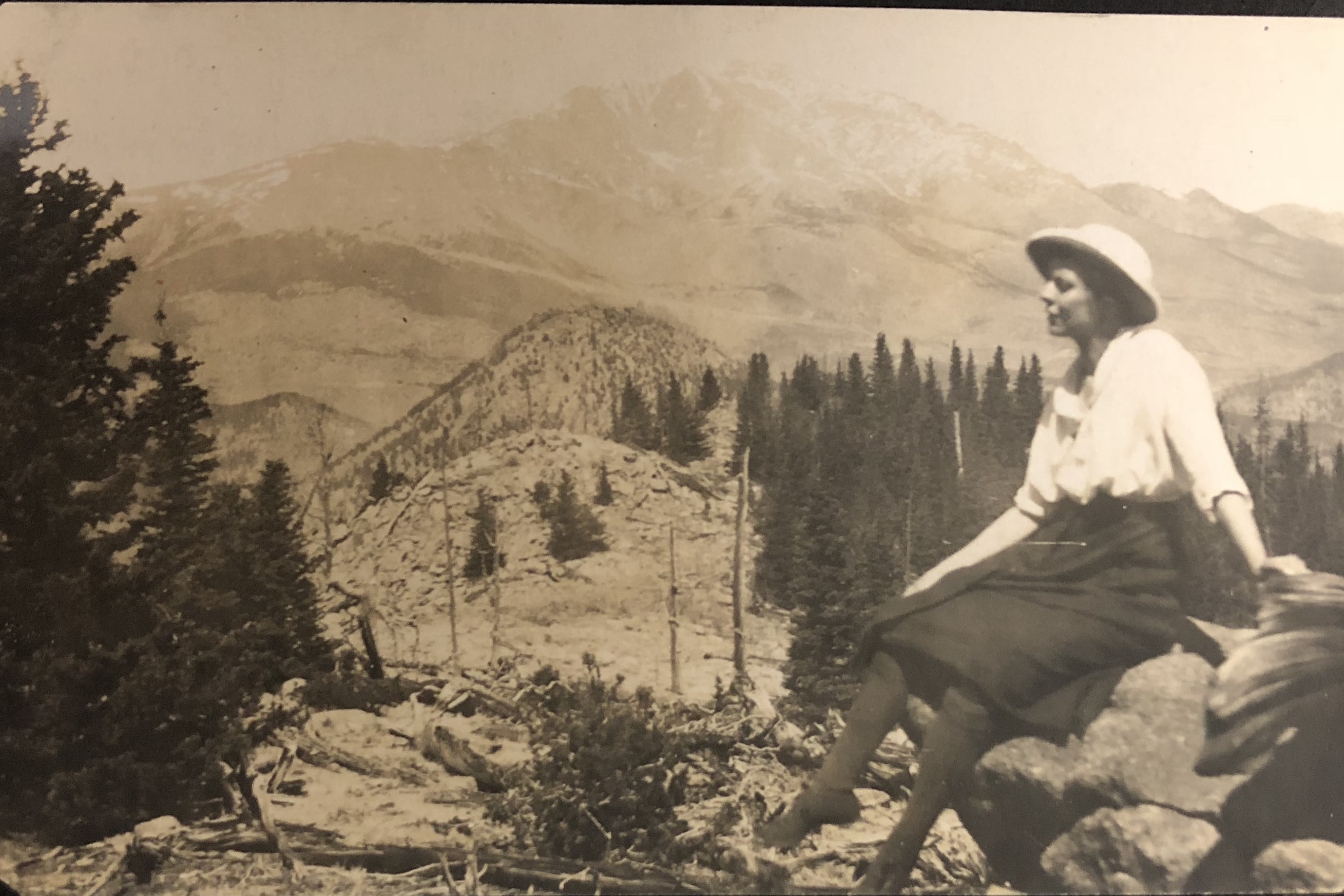 Woman in early 1900 dress at top of a mountain